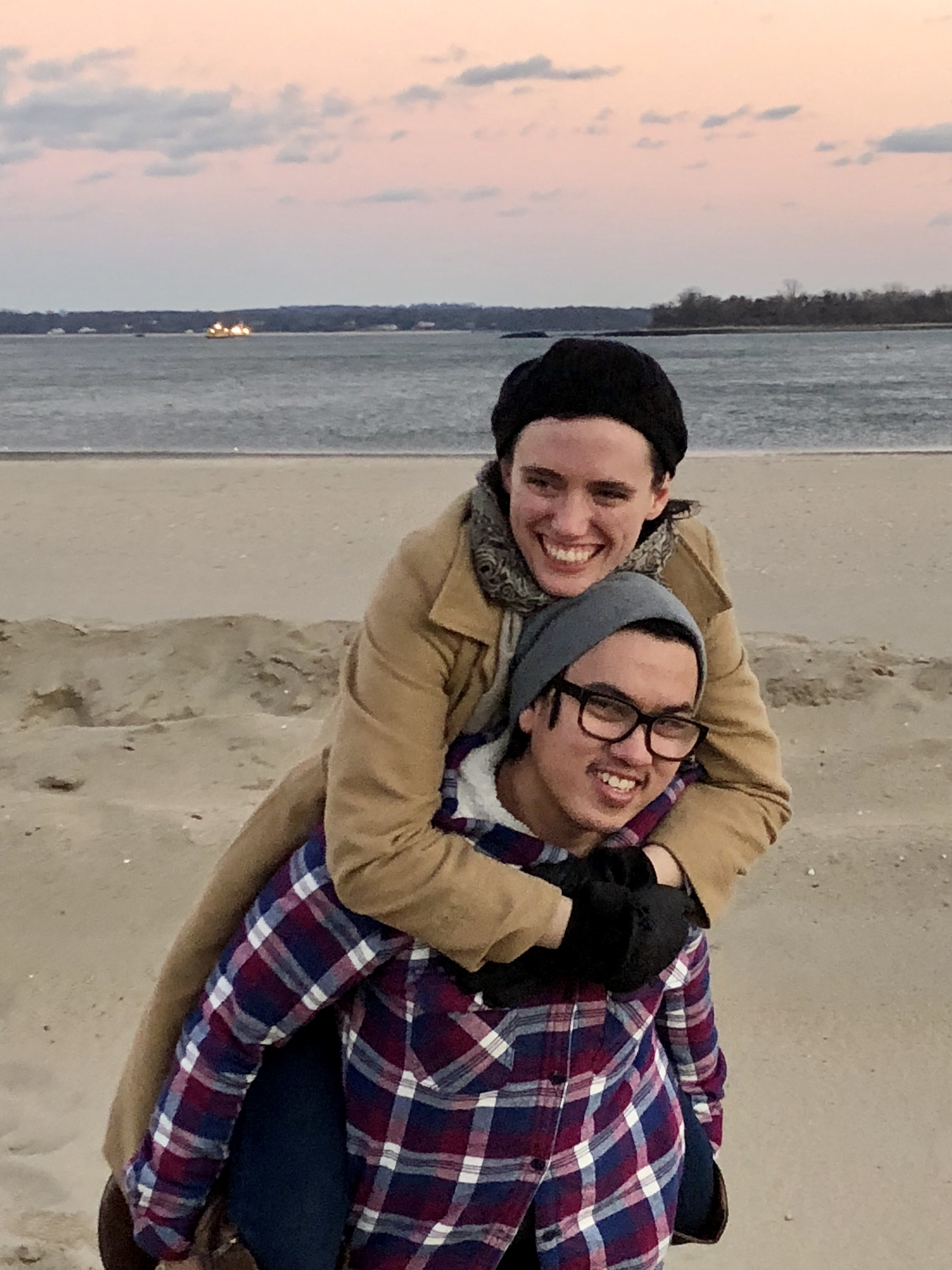 Tori (the author) clinging onto her husband's (Johnny) back as he carries her over the sand at orchard beach in the Bronx. The sun is setting over the water, the sky is pink. They are both wearing coats and hats. Both are grinning and looking away from the camera in opposite directions.